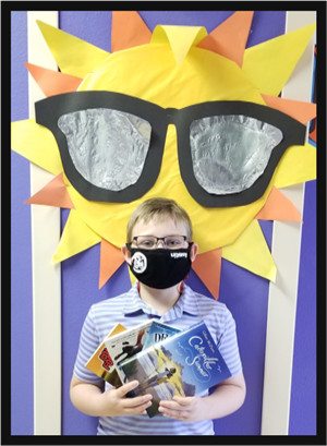 Student in a mask holding several books, standing in front of a picture of the sun.